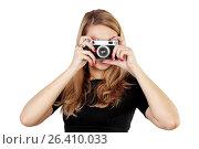 Купить «Молодая девушка на белом фоне держит фотокамеру в руках и фотографирует», фото № 26410033, снято 7 декабря 2013 г. (c) Александр Гаценко / Фотобанк Лори