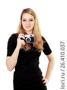 Купить «Молодая девушка на белом фоне держит фотоаппарат в руке», фото № 26410037, снято 7 декабря 2013 г. (c) Александр Гаценко / Фотобанк Лори