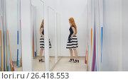 Купить «A girl trying on a dress in front of a mirror in a women's clothing store», фото № 26418553, снято 17 августа 2018 г. (c) Константин Шишкин / Фотобанк Лори