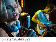 Купить «Female singer singing on vintage microphone», фото № 26440829, снято 7 марта 2017 г. (c) Wavebreak Media / Фотобанк Лори