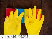 Купить «Yellow gloves with scouring pad on a wooden floor», фото № 26446645, снято 21 октября 2016 г. (c) Wavebreak Media / Фотобанк Лори