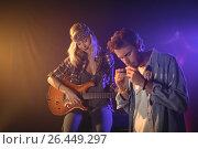 Купить «Guitarist performing with musician playing harmonica in nightclub», фото № 26449297, снято 7 марта 2017 г. (c) Wavebreak Media / Фотобанк Лори