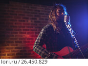 Купить «Male singer performing with guitar in nightclub», фото № 26450829, снято 7 марта 2017 г. (c) Wavebreak Media / Фотобанк Лори