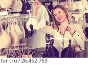 Купить «Smiling female shopper examining bras in shop», фото № 26452753, снято 20 марта 2017 г. (c) Яков Филимонов / Фотобанк Лори