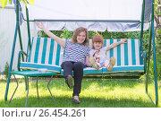 Купить «Маленькая девочка с мамой на качелях-диване на дачном участке», фото № 26454261, снято 31 мая 2017 г. (c) Гетманец Инна / Фотобанк Лори