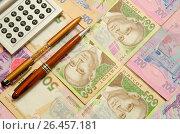 Купить «Две авторучки и калькулятор лежат на банкнотах украинских гривен», фото № 26457181, снято 14 мая 2017 г. (c) Игорь Кутателадзе / Фотобанк Лори