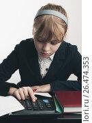 Купить «School girl using calculator, closeup portrait», фото № 26474353, снято 6 апреля 2014 г. (c) EugeneSergeev / Фотобанк Лори