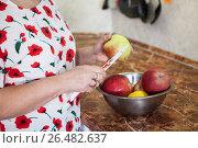 Купить «Женщина чистит и режет яблоко ножом на кухне», фото № 26482637, снято 6 ноября 2016 г. (c) Кекяляйнен Андрей / Фотобанк Лори