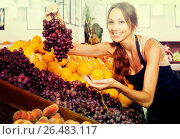 Купить «Woman in apron selling ripe grapes in shop», фото № 26483117, снято 1 апреля 2020 г. (c) Яков Филимонов / Фотобанк Лори