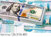 Купить «Stack of one hundred american dollar banknotes over roubles background», фото № 26519481, снято 9 января 2017 г. (c) FotograFF / Фотобанк Лори