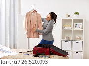 Купить «woman with smartphone packing travel bag at home», фото № 26520093, снято 18 января 2017 г. (c) Syda Productions / Фотобанк Лори