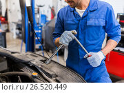 Купить «mechanic man with wrench repairing car at workshop», фото № 26520449, снято 1 июля 2016 г. (c) Syda Productions / Фотобанк Лори