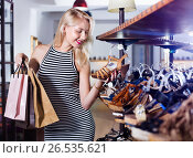 Купить «Glad woman shopping pair of new shoes», фото № 26535621, снято 25 апреля 2019 г. (c) Яков Филимонов / Фотобанк Лори