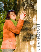 Купить «Woman in autumn relaxing embracing a tree», фото № 26537481, снято 8 октября 2008 г. (c) age Fotostock / Фотобанк Лори