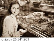 Купить «Smiling girl choosing delicious ganaches, praline and chocolates», фото № 26541961, снято 31 марта 2020 г. (c) Яков Филимонов / Фотобанк Лори