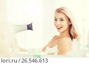 Купить «happy young woman with fan drying hair at bathroom», фото № 26546613, снято 13 февраля 2016 г. (c) Syda Productions / Фотобанк Лори