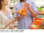 Купить «couple with smartphone buying oranges at grocery», фото № 26546809, снято 21 октября 2016 г. (c) Syda Productions / Фотобанк Лори