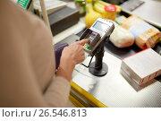 Купить «woman entering pin code at store cash register», фото № 26546813, снято 21 октября 2016 г. (c) Syda Productions / Фотобанк Лори