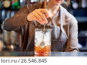 Купить «bartender with cocktail stirrer and glass at bar», фото № 26546845, снято 7 февраля 2017 г. (c) Syda Productions / Фотобанк Лори