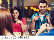 happy friends taking picture of food at restaurant. Стоковое фото, фотограф Syda Productions / Фотобанк Лори
