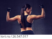 young woman flexing muscles in gym. Стоковое фото, фотограф Syda Productions / Фотобанк Лори