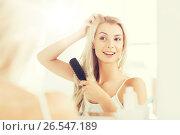 Купить «happy woman brushing hair with comb at bathroom», фото № 26547189, снято 13 февраля 2016 г. (c) Syda Productions / Фотобанк Лори
