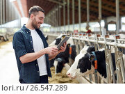 Купить «young man with tablet pc and cows on dairy farm», фото № 26547289, снято 12 августа 2016 г. (c) Syda Productions / Фотобанк Лори