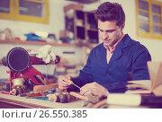 Купить «Carpenter working in studio», фото № 26550385, снято 8 апреля 2017 г. (c) Яков Филимонов / Фотобанк Лори