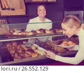Купить «Woman offering deserts in the pastry shop», фото № 26552129, снято 26 февраля 2020 г. (c) Яков Филимонов / Фотобанк Лори