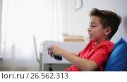 Купить «happy boy with gamepad playing video game at home», видеоролик № 26562313, снято 23 мая 2019 г. (c) Syda Productions / Фотобанк Лори