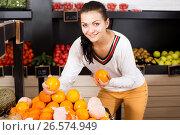 Купить «Female customer examining various fruits», фото № 26574949, снято 23 ноября 2016 г. (c) Яков Филимонов / Фотобанк Лори