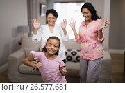 Купить «Portrait of smiling girl dancing with family», фото № 26577681, снято 15 марта 2017 г. (c) Wavebreak Media / Фотобанк Лори