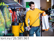 Купить «Young man choosing garden sprayer in garden equipment shop», фото № 26581961, снято 2 марта 2017 г. (c) Яков Филимонов / Фотобанк Лори