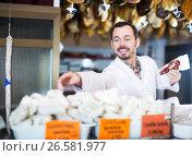 Купить «Seller offering displayed sorts of meat», фото № 26581977, снято 2 января 2017 г. (c) Яков Филимонов / Фотобанк Лори
