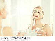 happy woman applying cream to face at bathroom. Стоковое фото, фотограф Syda Productions / Фотобанк Лори