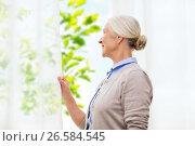 Купить «happy senior woman looking through window at home», фото № 26584545, снято 10 июля 2015 г. (c) Syda Productions / Фотобанк Лори