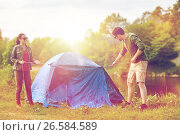 Купить «happy couple setting up tent outdoors», фото № 26584589, снято 27 мая 2016 г. (c) Syda Productions / Фотобанк Лори