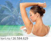 Купить «woman with antiperspirant deodorant over beach», фото № 26584629, снято 9 апреля 2017 г. (c) Syda Productions / Фотобанк Лори