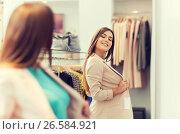 Купить «happy woman posing at mirror in clothing store», фото № 26584921, снято 19 февраля 2016 г. (c) Syda Productions / Фотобанк Лори
