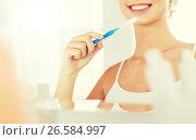 Купить «woman with toothbrush cleaning teeth at bathroom», фото № 26584997, снято 13 февраля 2016 г. (c) Syda Productions / Фотобанк Лори