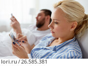 Купить «couple with smartphones in bed at home», фото № 26585381, снято 11 февраля 2017 г. (c) Syda Productions / Фотобанк Лори