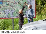 Пожилая пара определяет свое местонахождение на автомобильной трассе по карте на информационном щите. Стоковое фото, фотограф Кекяляйнен Андрей / Фотобанк Лори