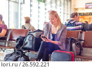 Купить «Female traveler using cell phone while waiting on airport», фото № 26592221, снято 18 февраля 2019 г. (c) Matej Kastelic / Фотобанк Лори