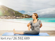 Купить «woman doing yoga in twist pose on beach», фото № 26592689, снято 13 ноября 2015 г. (c) Syda Productions / Фотобанк Лори