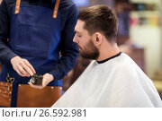 Купить «barber showing hair styling wax to male customer», фото № 26592981, снято 6 апреля 2017 г. (c) Syda Productions / Фотобанк Лори