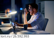 angry businessman with smartphone at night office. Стоковое фото, фотограф Syda Productions / Фотобанк Лори