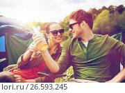 Купить «happy couple clinking drinks at campsite tent», фото № 26593245, снято 27 мая 2016 г. (c) Syda Productions / Фотобанк Лори