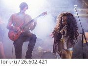 Купить «Cheeful female singer with male guitarist performing at nightclub», фото № 26602421, снято 7 марта 2017 г. (c) Wavebreak Media / Фотобанк Лори