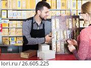 Купить «Seller offering door hinges to female», фото № 26605225, снято 5 апреля 2017 г. (c) Яков Филимонов / Фотобанк Лори