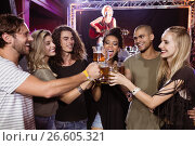 Купить «Smiling friends toasting beer glasses with performer singing in background», фото № 26605321, снято 7 марта 2017 г. (c) Wavebreak Media / Фотобанк Лори